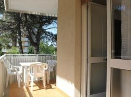 appartamento con balcone e un ombrellone con due lettini in spiaggia